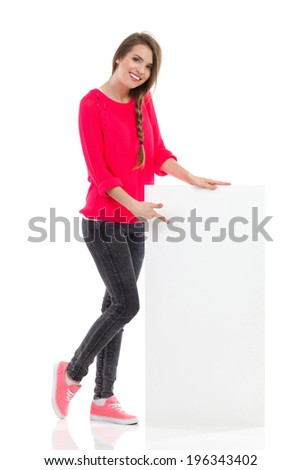 Cheerful young woman is standing close to blank placard and pointing. Full length studio shot isolated on white. - stock photo
