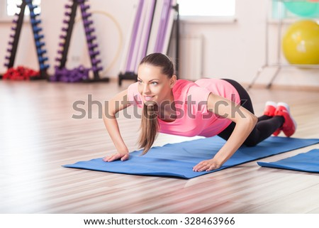 Cheerful young woman is training her boy in fitness center. The lady is doing press-up. She is looking forward and smiling - stock photo