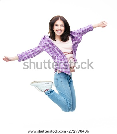 Cheerful young woman jumping over gray background. Looking at camera - stock photo