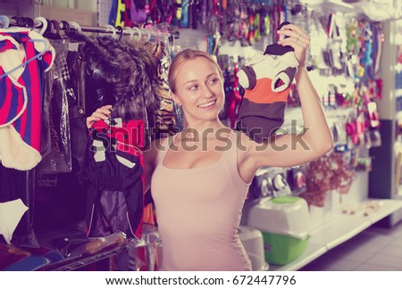 Cheerful young woman looking through different clothes for dog in pet shop