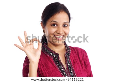 Cheerful young woman making OK sign - stock photo