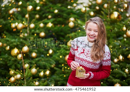 Cheerful young woman on a street of Paris decorated for Christmas, unpacking Christmas present