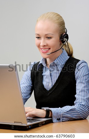 Cheerful young woman - Operator of call center with headset, looking in laptop