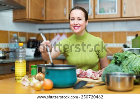 Cheerful young woman preparing meal at home and smiling - stock photo