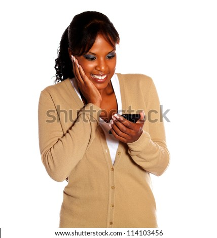 Cheerful young woman reading a message on cellphone on isolated background - stock photo