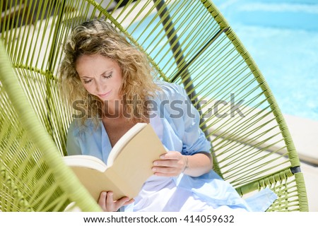 cheerful young woman reading in a hammock by the pool on sunny summer day - stock photo