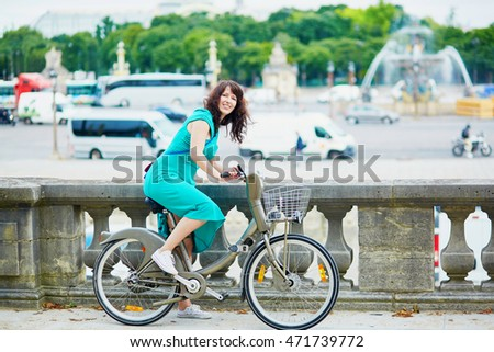 Cheerful young woman riding a bicycle on a street of Paris