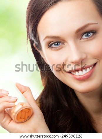 Cheerful young woman showing bottle with pills, outdoor - stock photo