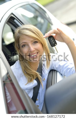Cheerful young woman showing car key