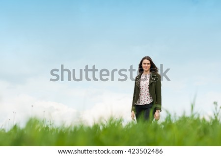 Cheerful young woman standing outside on green meadow in sunny day with clear sky in background - stock photo