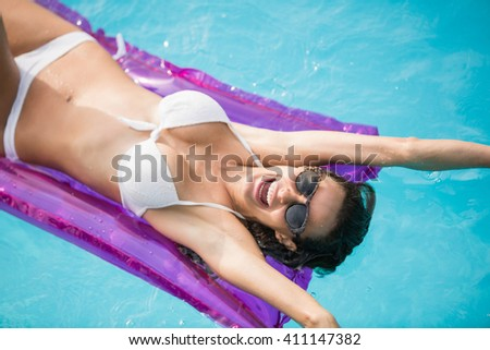 Cheerful young woman swimming with inflatable raft at pool - stock photo