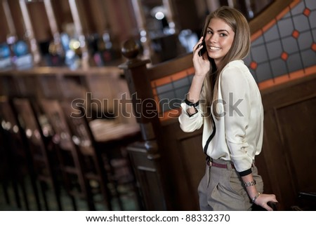 cheerful young woman talking on a cell phone in the interior of the bar