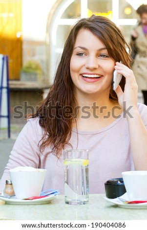 Cheerful young woman talking on the phone in a cafe