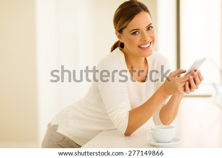 cheerful young woman using smart phone at home - stock photo
