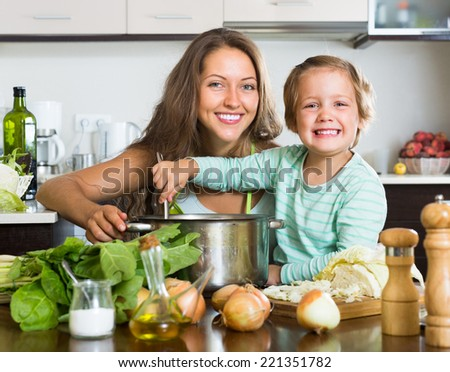 Cheerful young woman with little daughter cooking with vegetables at home kitchen. Focus on woman  - stock photo