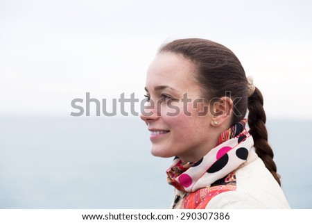 Cheerful young woman with plait posing at quay - stock photo