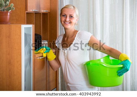 Cheerful young woman with rubber gloves cleaning indoors  - stock photo