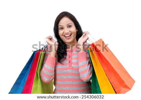 Cheerful young woman with shopping bags against white background