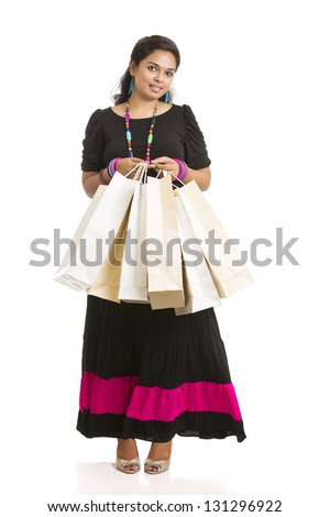 Cheerful Young woman with shopping bags over white background - stock photo