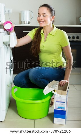 Cheerful young woman with washing detergent doing laundry at home