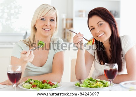 Cheerful young Women eating salad in a kitchen - stock photo