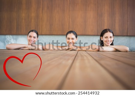 Cheerful young women in swimming pool against heart - stock photo