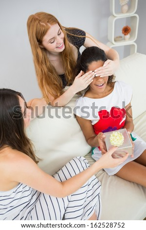 Cheerful young women surprising friend with a gift on sofa at home