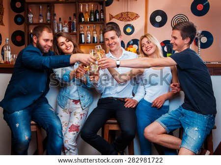 cheerful youth company is celebrating with champagne at bar. horizontal photo - stock photo