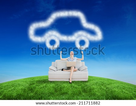 Cheering beautiful businesswoman sitting on couch against green hill under blue sky - stock photo