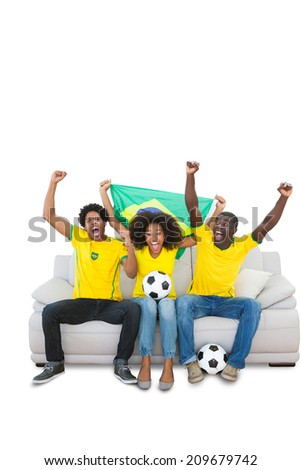 Cheering brazilian football fans in yellow on the sofa on white background - stock photo