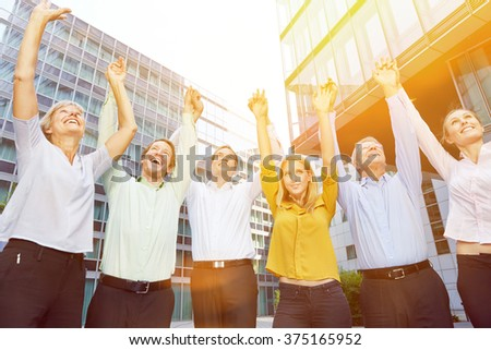 Cheering business people pulling their arms up together in summer - stock photo