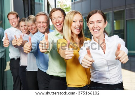 Cheering business people team holding thumbs up next to the office - stock photo