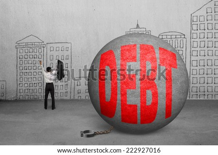 cheering businessman free from debt ball shackle with doodles wall - stock photo