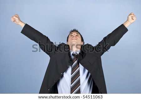 Cheering businessman winning something or having a successful business standing with arms raised and looking up on blue background - stock photo