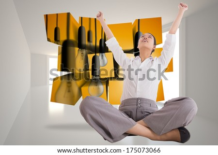 Cheering businesswoman sitting cross legged against bright hall with windows - stock photo