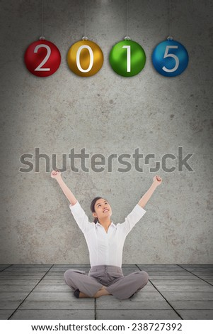 Cheering businesswoman sitting cross legged against grey room - stock photo