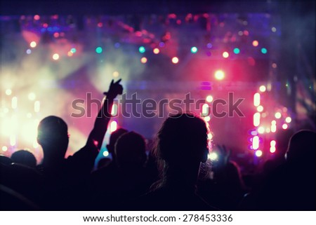 Cheering crowd in front of bright colorful stage lights - retro styled photo  - stock photo