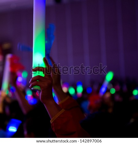 cheering crowd with hands up at concert. - stock photo