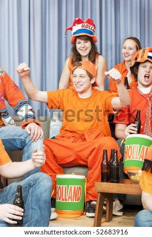 Cheering fan, with his arms raised, surrounded by a group of his friends, watching a game at home - stock photo