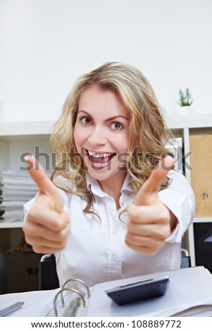 Cheering female student at desk holding both her thumbs up - stock photo