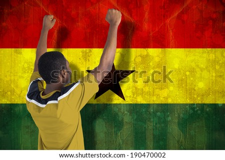 Cheering football fan in yellow jersey against ghana flag in grunge effect - stock photo