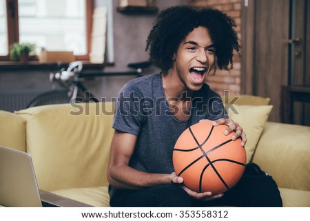 Cheering for his favorite basketball team. Cheerful young African man watching TV and holding basketball ball while sitting on the couch at home - stock photo