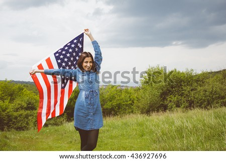 Cheering girl waving the American flag, while posing in spectacular green backgrounds, on cloudy day.