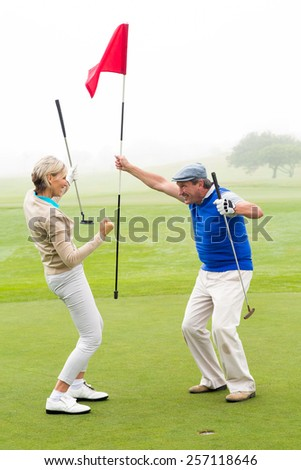 Cheering golfing couple on a foggy day at the golf course - stock photo