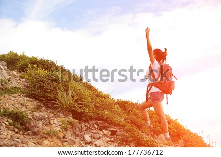 cheering happy asian woman hiker open arms at mountain peak - stock photo