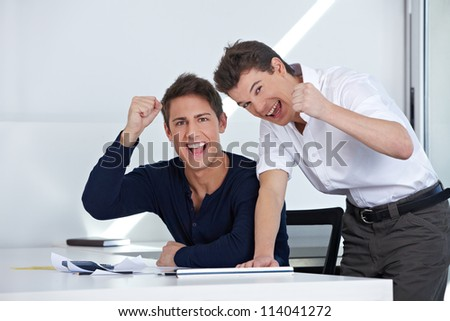 Cheering happy business people clenching their fists in the office - stock photo