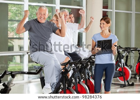 Cheering happy senior citizens with fitness trainer in gym - stock photo