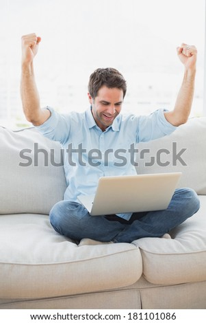 Cheering man using laptop sitting on sofa at home in the living room - stock photo