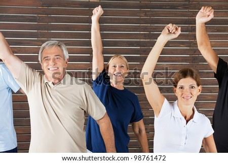 Cheering senior citizens at workout in fitness center gym - stock photo