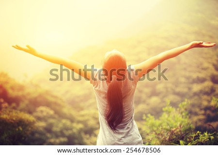 cheering woman enjoy the beautiful view at mountain peak  - stock photo